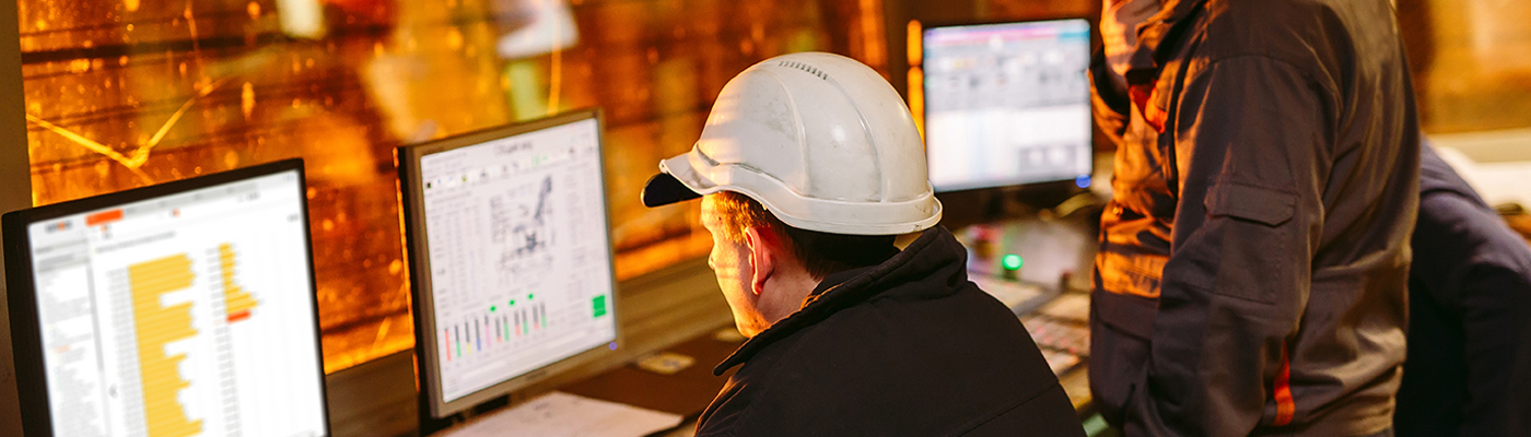 Project personel, security staff looking at computer screes in front of a window to production facility. Computer screen shows app.keepfocus