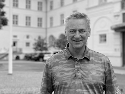 Christian is a mature man in his 50's, short blond hair and smiling in from of Vejlsøhus' white main building